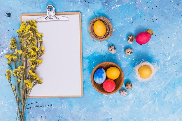 클립 보드와 테이블에 꽃 부활절 달걀