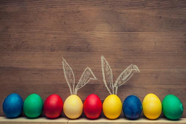 Пасхальные яйца с милыми кроличьими ушками на деревянном фоне