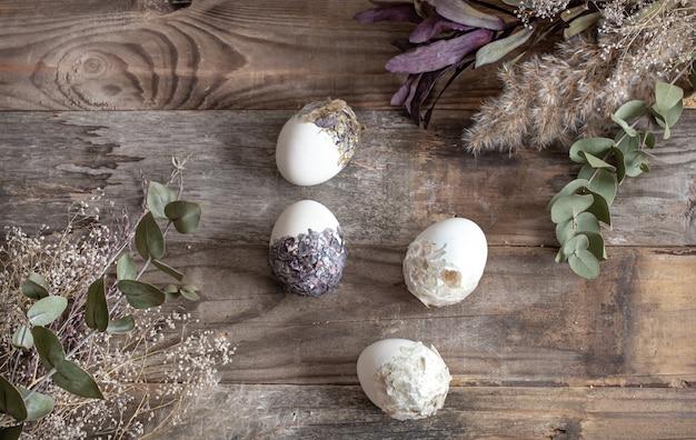 나무 테이블에 말린 된 꽃과 함께 부활절 달걀. 행복 한 부활절 개념입니다. 프리미엄 사진