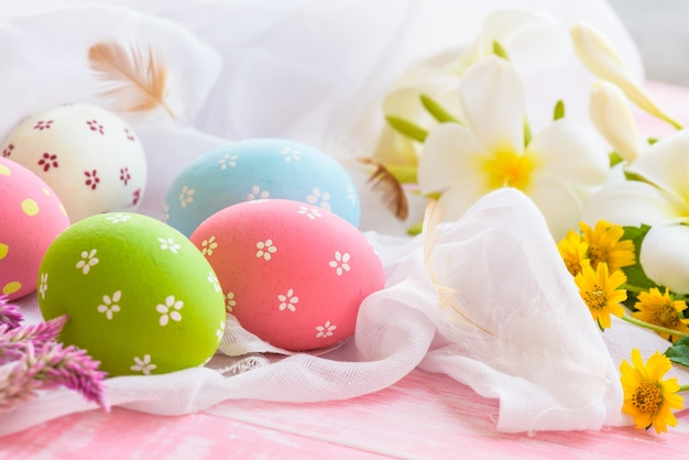 Easter eggs with flower on white cheesecloth and  pink wooden background.