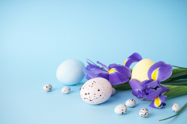 Easter eggs with flowers on a blue surface, place for text.