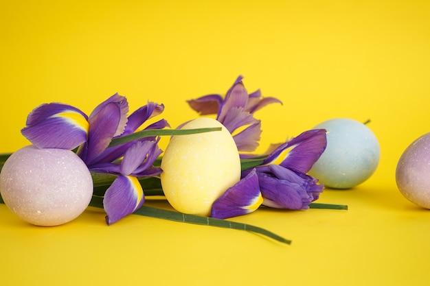 Пасхальные яйца с цветами на желтом фоне.