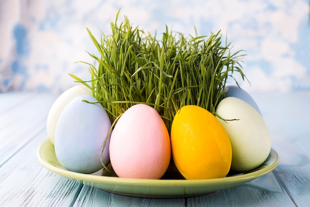 Easter eggs with grass served on the plate on a blue surface