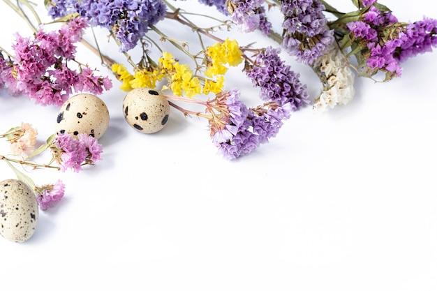 Пасхальные яйца с сиреневыми и желтыми полевыми цветами на белом фоне