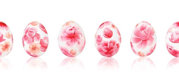 赤い花柄のイースターエッグ。白い孤立した背景にイースター色の卵のシームレスなパターン。