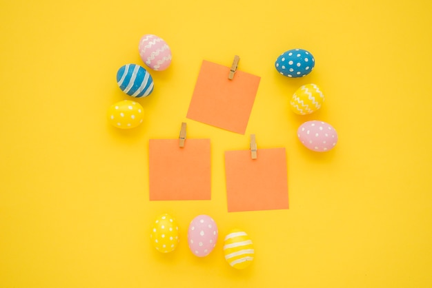 Easter eggs with small blank papers on table