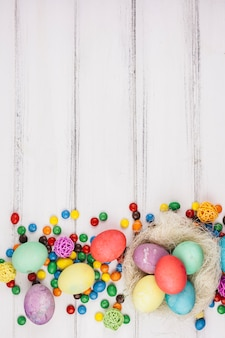 Easter eggs with small candies on table