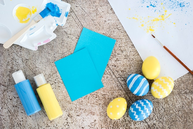 Easter eggs with small papers and glue sticks on table