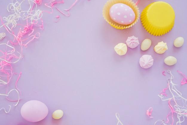 Пасхальные яйца с маленькими сладостями на фиолетовом столе