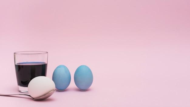 Uova di pasqua con cucchiaio e vetro con vernice