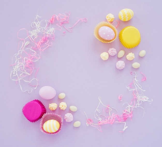 Easter eggs with sweets on purple table