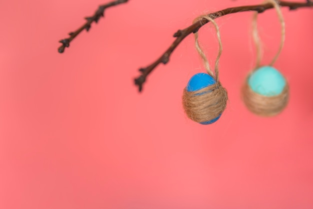 Easter eggs with thread hanging on twig