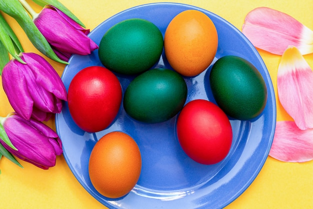 Easter eggs with tulips on a blue dish on a yellow .