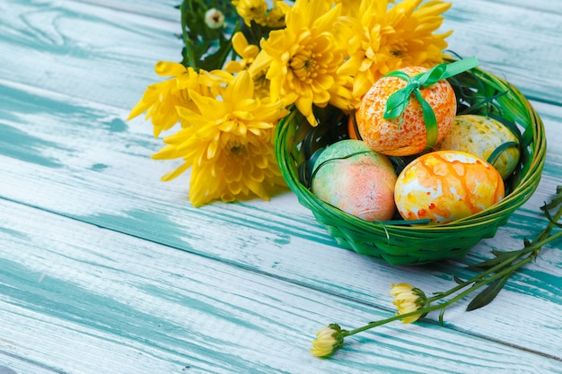 Easter eggs with tulips on blue wooden