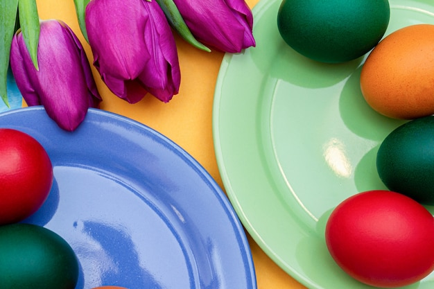 Easter eggs with tulips on a colorful dishes on a yellow .