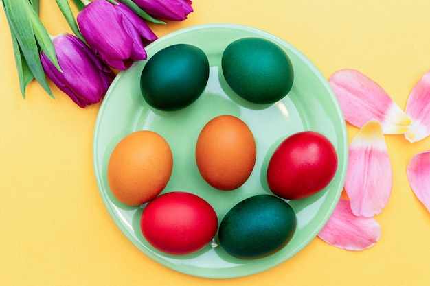Easter eggs with tulips on a green dish on a yellow .