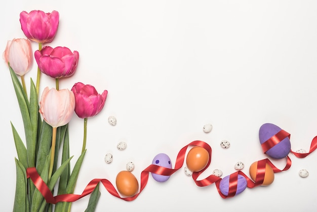 Easter eggs with tulips on table