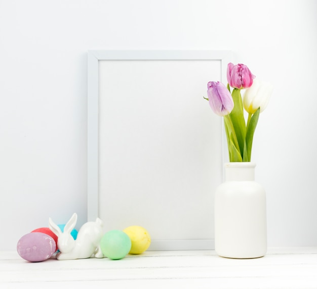 Easter eggs with tulips in vase and blank frame