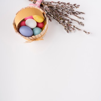 Easter eggs in wooden basket with willow branches
