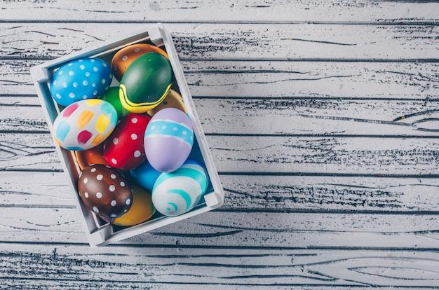 Uova di pasqua in scatola di legno su fondo di legno leggero.