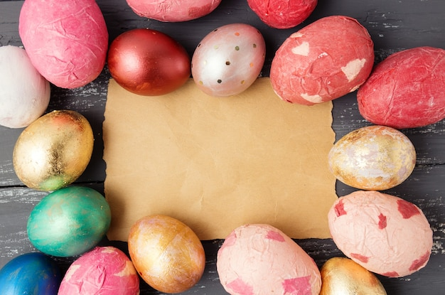 Easter eggs on wooden table with blank paper for text. holiday background