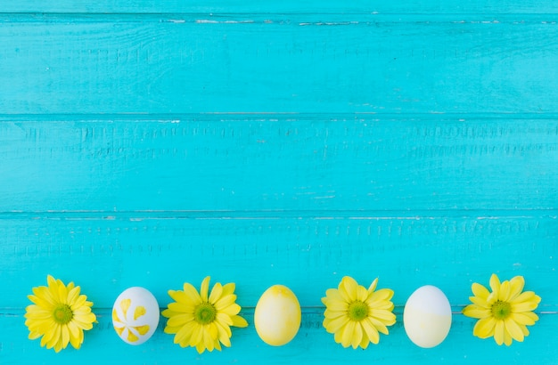 Easter eggs and yellow flowers on desk