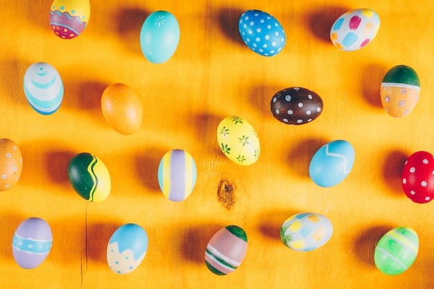 Easter eggs on yellow wooden background.