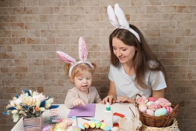 イースター、家族、休日、子供のコンセプト-イースターのために卵を着色する小さな女の子と母親のクローズアップ