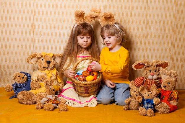 Семейное пасхальное фото мальчика и девочки с заячьими ушками и игрушками