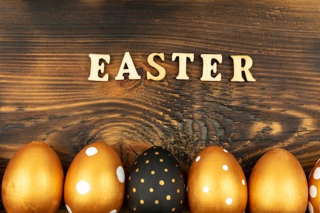 Пасхальный праздничный фон. вид сверху пасхальных яиц, окрашенных золотой краской и надписью на английской пасхе. деревянные буквы на фоне темного дерева.