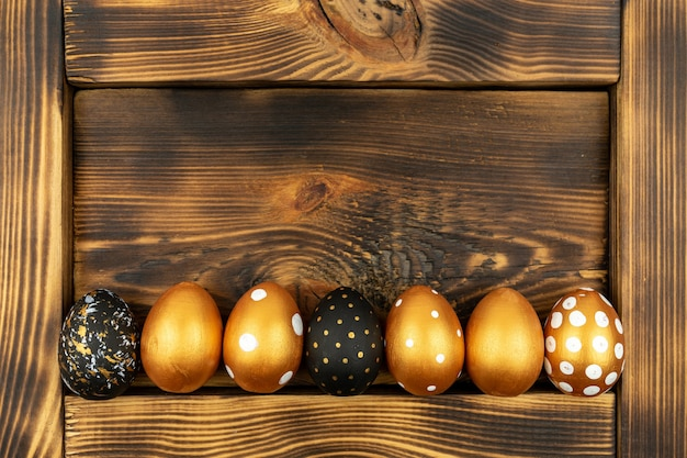 Пасхальный праздничный фон. вид сверху пасхальных яиц, окрашенных золотой краской на фоне темного дерева.