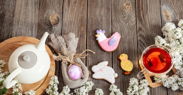 Пасхальный праздничный состав с пасхальными печеньями и чашкой чая на деревянном столе.