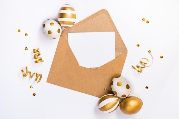 Пасхальное праздничное украшение. взгляд сверху пасхальных яиц и пустой карточки в конверте крафт.