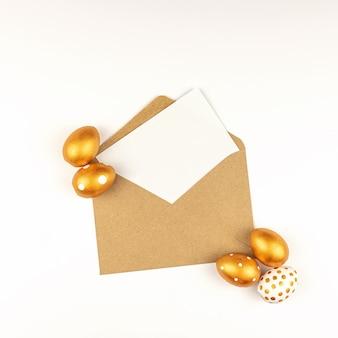 Пасхальное праздничное украшение. вид сверху на пасхальные яйца, окрашенные золотой краской, и пустой макет карты в крафт-конверте. различные пунктирные узоры. белый фон.