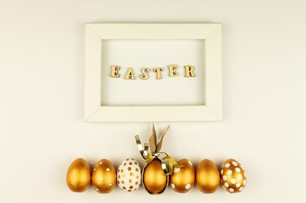 부활절 축제 장식. 황금 페인트와 빈 모형 사진 프레임으로 채색 된 부활절 달걀의 상위 뷰. 다양한 점선 디자인. 흰 바탕.