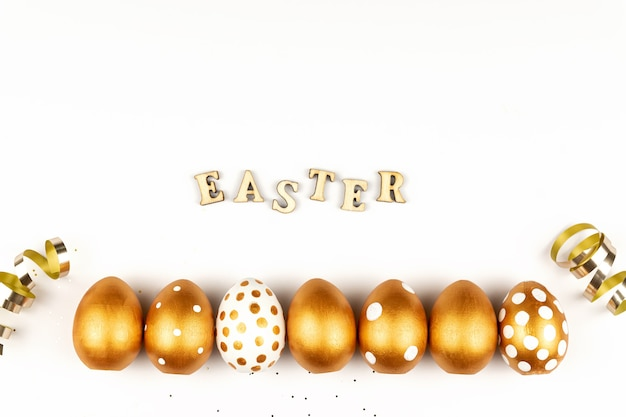 Пасхальное праздничное украшение. вид сверху пасхальных яиц, окрашенных золотой краской и надписью на английском языке happy easter. деревянные буквы на белом фоне. разнообразный точечный дизайн.