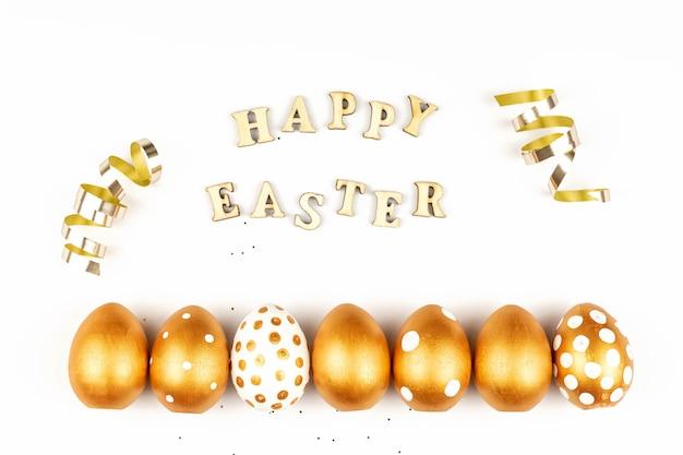 Пасхальное праздничное украшение. вид сверху пасхальных яиц, окрашенных золотой краской и надписью на английском языке happy easter.