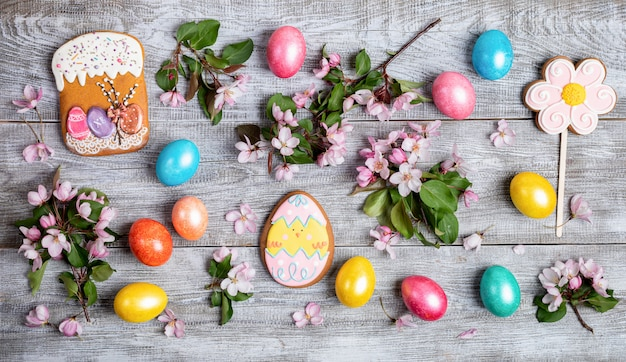 Easter festive layout of pink apple tree twigs, quail and painted hen eggs, multicolored gingerbreads on wooden table.