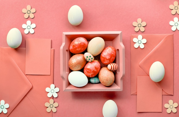 Easter flat lay in coral color with painted eggs, cards, envelopes and decorative flowers