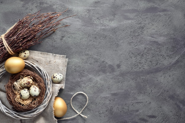 Easter flat lay on dark background with quail eggs in the nest, linen fabrique and two golden eggs on dark with copy-space