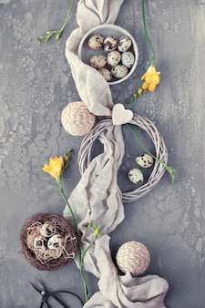 Easter flat lay on dark table with quail eggs in bird nest, linen textile and around.