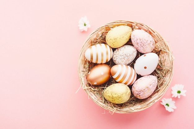 Easter flat lay of eggs in nest on pink