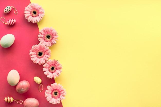 イースターフラットは黄色とサンゴ色で塗られた卵とガーベラヒナギク、コピースペースで横たわっていた