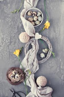 イースターフラットは、鳥の巣、リネンの織物などにウズラの卵が入った暗いテーブルの上に横たわっていました。