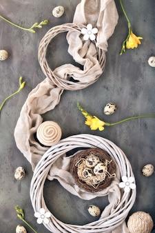 イースターフラットレイ、ウズラの卵、リネンタオルの上に鳥の巣。黄色いフリージアの花、籐の花輪。