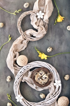 Easter flat lay, quail eggs and bird nest on linen towel. yellow freesia flowers, rattan wreath.