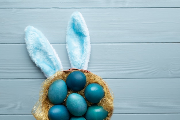 Easter flat lay with blue eggs in the basket and funny bunny ears on light blue wooden background. copy space
