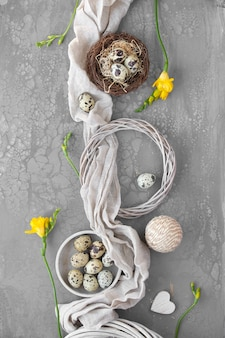 Easter flat lay with quail eggs in bird nest, linen textile and around. yellow freesia flowers and rattan wreath on textured board. natural easter decorations.