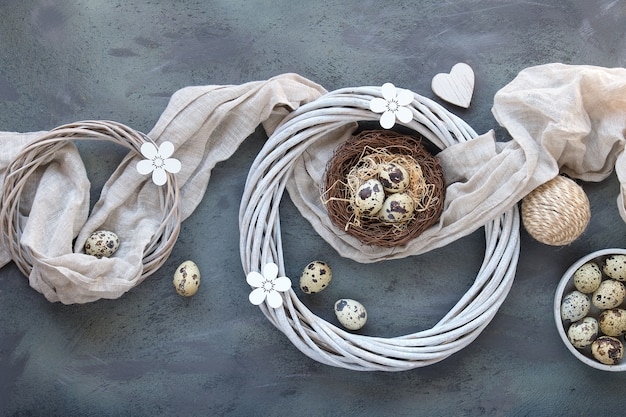 Easter flat lay with quail eggs in bird nest with linen textile. wooden flowers, rattan wreath.