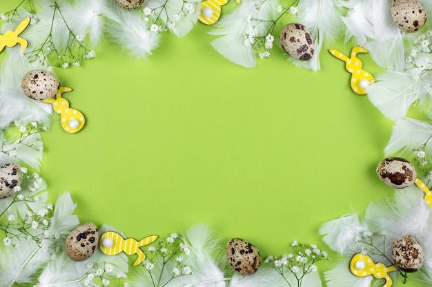 Easter flat lay with quail eggs, easter bunnys, flowers and white feathers on a green background.